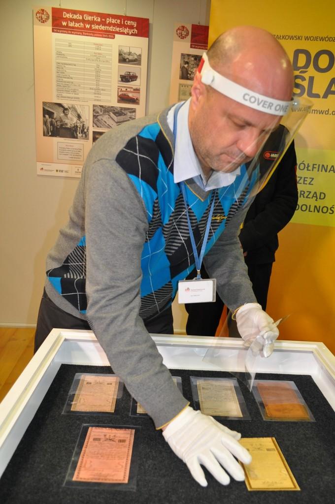 Jan Bałchan przyjmuje banknot do zbiorów muzeum.