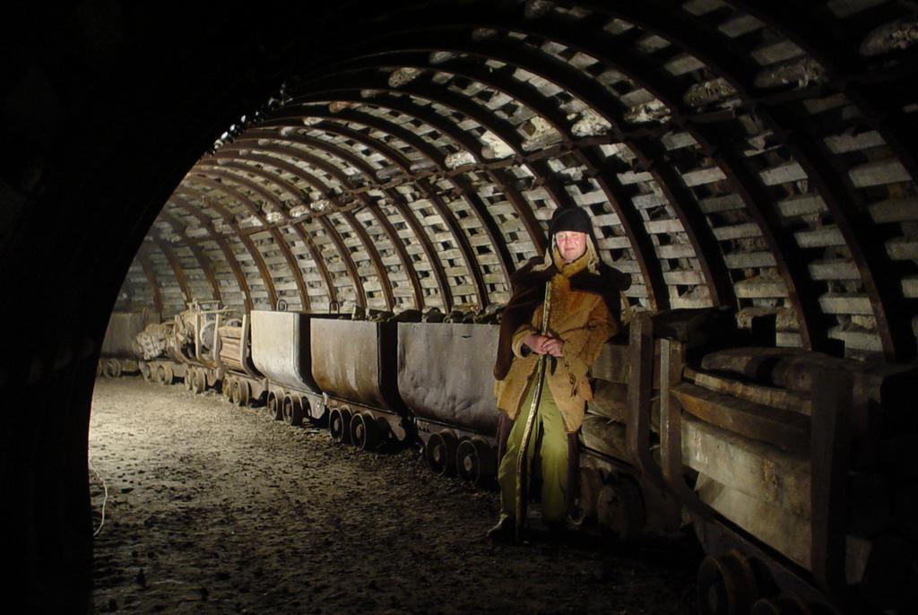 Chodnik w kopalni z kolejką podziemną i dawnym górnikiem